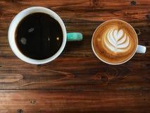 Кофе искусства черной кофейной чашки и latte на деревянном столе Стоковые Изображения RF