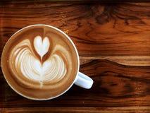 Кофе искусства Latte сердца в белой чашке на деревянном столе Стоковое Изображение RF
