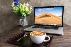 Кофе искусства Latte с компьютером macbook на деревянном столе стоковая фотография