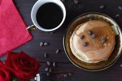 Кофе и блинчики завтрака на таблице с розами Стоковые Фото