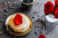 Кофе и блинчики завтрака на таблице с розами Стоковая Фотография