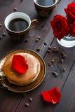 Кофе и блинчики завтрака на таблице с розами Стоковые Изображения