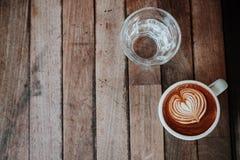 Кофе и вода искусства latte взгляд сверху на деревянном столе Закройте вверх по острословию Стоковое Изображение RF