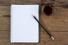 Кофе и карандаш тетради на деревянной таблице Стоковые Изображения RF