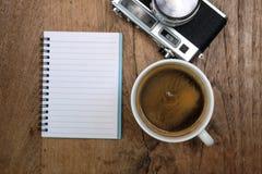 Кофе и классика камеры с тетрадью на деревянном Стоковое фото RF