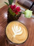 Кофе и цветки на таблице Стоковые Изображения