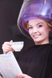 Кофе кассеты чтения девушки выпивая. Фен для волос в салоне красоты волос Стоковые Изображения