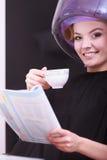 Кофе кассеты чтения девушки выпивая. Фен для волос в салоне красоты волос Стоковое Изображение