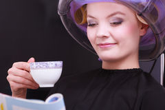 Кофе кассеты чтения девушки выпивая. Фен для волос в салоне красоты волос Стоковые Фотографии RF