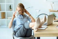кофе коммерсантки выпивая пока сидящ на рабочем месте с компьтер-книжкой Стоковая Фотография RF