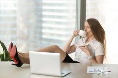 Кофе коммерсантки выпивая с ногами на столе Стоковое Фото