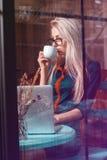 Кофе коммерсантки красоты выпивая и портативный компьютер i использования Стоковое Фото