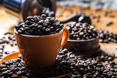 Кофе Кофейная чашка вполне кофейных зерен, механизма настройки радиопеленгатора на заднем плане Стоковые Фото