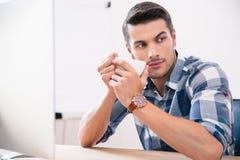 Кофе красивого бизнесмена выпивая в офисе Стоковые Фото