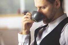 Кофе красивого бизнесмена выпивая на рабочем месте Стоковые Фотографии RF