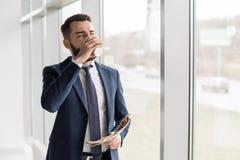 Кофе красивого бизнесмена выпивая окном Стоковые Изображения RF