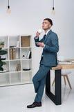 Кофе красивого молодого бизнесмена выпивая пока полагающся на таблице офиса Стоковая Фотография