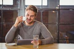 Кофе красивого человека выпивая и смотреть таблетку стоковое фото rf