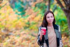 Кофе красивой женщины выпивая в парке осени под листопадом кофе идет к Стоковое Фото