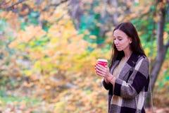 Кофе красивой женщины выпивая в парке осени под листопадом кофе идет к Стоковые Изображения