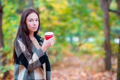Кофе красивой женщины выпивая в парке осени под листопадом Кофе, который нужно пойти в ее руки Стоковая Фотография RF