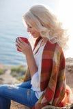 Кофе красивой женщины выпивая сидя на скалистом береге Стоковые Фотографии RF