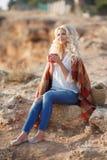 Кофе красивой женщины выпивая сидя на скалистом береге Стоковое фото RF
