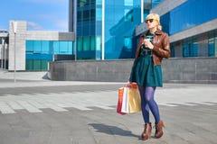 Кофе красивой женщины выпивая с хозяйственными сумками Стоковая Фотография