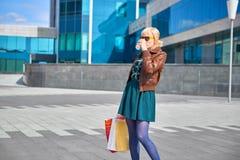 Кофе красивой женщины выпивая с хозяйственными сумками Стоковое Фото