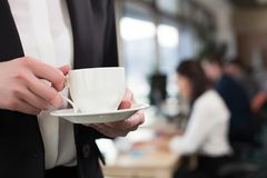 Кофе красивой коммерсантки выпивая в офисе Стоковая Фотография