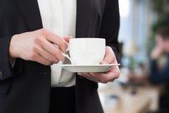 Кофе красивой коммерсантки выпивая в офисе Стоковое Изображение RF