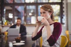 Кофе красивой молодой женщины выпивая от чашки на кафе Стоковые Фотографии RF