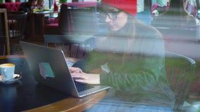 Кофе красивой молодой женщины работая и выпивая в кафе акции видеоматериалы