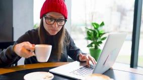 Кофе красивой молодой женщины работая и выпивая в кафе сток-видео