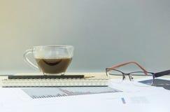 Кофе крупного плана черный в прозрачной чашке кофе на блокноте и карандаше с бумагой работы на te запачканного деревянного стола  Стоковые Фотографии RF