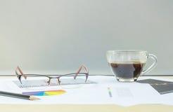 Кофе крупного плана черный в прозрачной чашке кофе с бумагой работы на запачканной деревянной стене стола и матированного стекла  Стоковые Изображения