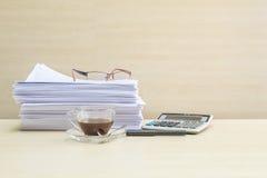 Кофе крупного плана черный в прозрачной чашке кофе с кучей бумаги и калькулятора работы на запачканном деревянных текстурированны Стоковая Фотография