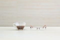 Кофе крупного плана черный в прозрачной чашке кофе с eyeglasses на запачканных деревянных столе и стене текстурировал предпосылку Стоковое фото RF