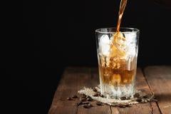 Кофе льда в высокорослом стекле сверх и кофейных зернах на старое деревенском Стоковое фото RF