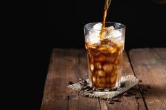 Кофе льда в высокорослом стекле сверх и кофейных зернах на старом деревенском деревянном столе Холодное питье лета на темной пред Стоковые Фотографии RF