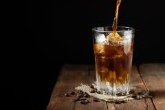 Кофе льда в высокорослом стекле сверх и кофейных зернах на старом деревенском деревянном столе Холодное питье лета на темной пред Стоковое фото RF