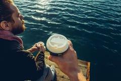Кофе людей выпивая сидя на пристани и наслаждаясь видом на море, съемкой точки зрения Стоковая Фотография
