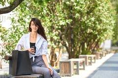Кофе милого брюнет выпивая сидя на деревянной скамье около бумажных сумок стоковые изображения
