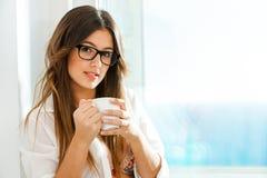 Кофе милой девушки выпивая на окне. Стоковые Изображения