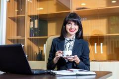 Кофе милой женщины выпивая на таблице в офисе Стоковое Изображение RF
