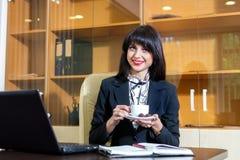 Кофе милой женщины выпивая на таблице Стоковая Фотография