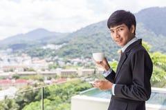 Кофе молодого азиатского бизнесмена выпивая Стоять на террасе Стоковые Изображения