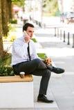 Кофе молодого бизнесмена есть и выпивая пока говорящ на телефоне Стоковая Фотография