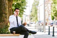 Кофе молодого бизнесмена есть и выпивая пока говорящ на телефоне Стоковые Фото