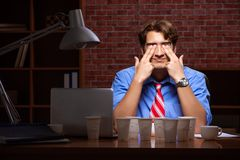 Кофе молодого работника выпивая работая вечером перенос стоковые изображения
